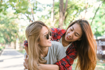 Happy young asian women couple playing to each other while they do city trip in warm sunlight morning weekend. City and nature lifestyle of Young women. Lifestyle in the city activity concept.