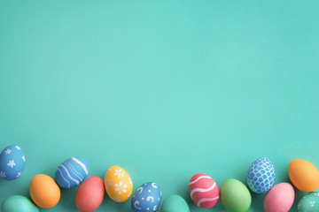 Happy Easter! Turquoise background with colorful easter eggs. Top view with copy space.