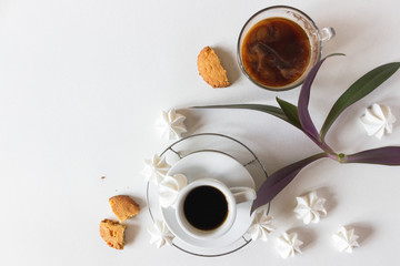 Creative layout. Coffee in a white and transparent cup on a white background with meringues . Green flower leaves. Flat lay