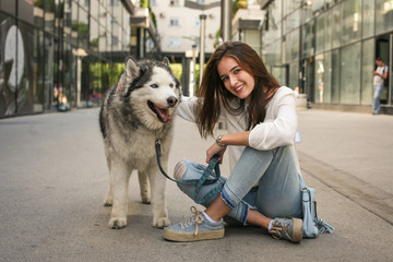 Teen girl poses to camera with her husky.