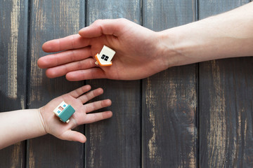 two tiny figurines, toys, models of houses lies on the open hand