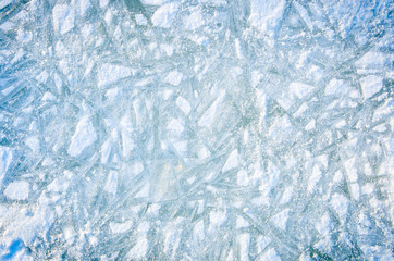 Textured background of white and blue ice with snow patterns.