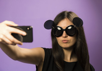Young Woman Make Selfie in Sunglasses on Purple Background. Photo in Googles on the Latest Iphone X