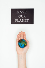 cropped image of woman holding earth model on hand under sign save our planet isolated on white, earth day concept