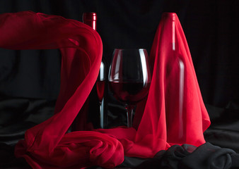 Bottle and glass of red wine with red silk .