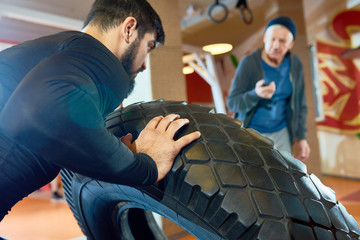 Portrait of bearded Middle-Eastern man flipping tire during training with coach in martial arts club, copy space
