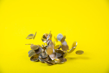 Falling coins money on yellow background, business wealth concept.