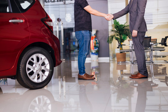 Businessman in formal suit handshaking with other partner in car background in showroom - successful partnership and deal concept.