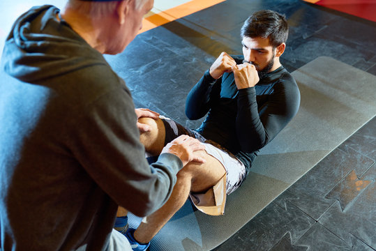 High angle portrait of strong bearded Middle-eastern man doing crunches preparing for fight practice with coach in martial arts club, copy space