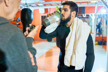 Waist up portrait of bearded Middle-eastern man drinking water after tough training in martial arts club, copy space