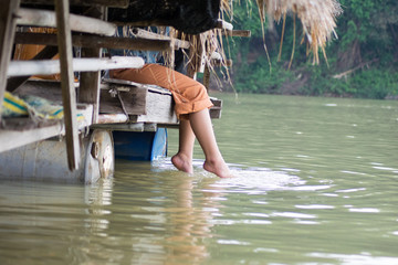 Woman relaxes by the lake sitting on the edge of a wooden jetty , swing one's feet near the water surface.floating market