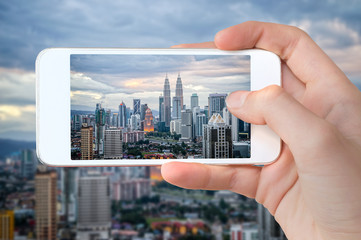Closeup of a hand with smartphone taking a picture of Kuala Lumpur skyline, Malaysia