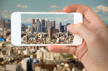 Closeup of a hand with smartphone taking a picture of Tokyo skyline, Shinjuku buildings, Japan
