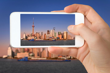 Closeup of a hand with smartphone taking a picture of Shanghai skyline and the Huangpu river, China