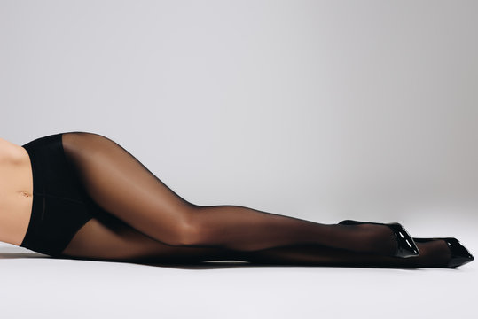 Seductive woman in black tights and shoes lying on white background