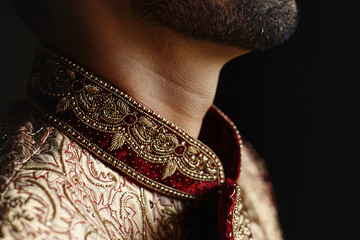 Thoughtful Indian groom stands with closed eyes wearing red sherwani with golden design