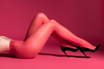 Female thin legs in red nylon tights and heel shoes on red background