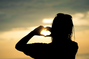 silhouette of a woman with her hands forming a heart, at sunset on the beach