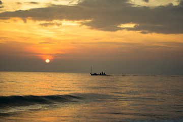 silhouette of fishing boat on sunset sea