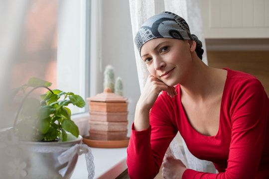 Young positive adult female cancer patient sitting in the kitchen by a window, smiling and looking at the camera.
