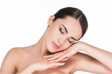 attractive young woman with eyes shut lying on hands isolated on white
