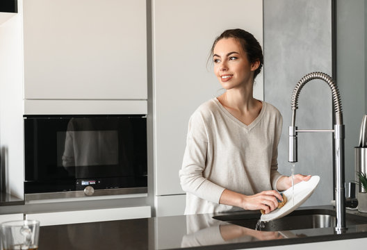 Portrait of a beautiful young woman washing dishes