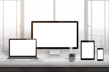 Wall Mural - Responsive web site design mockup. Computer displaz, laptop, tablet and smart phone on office desk. Window and sun light in background.