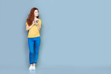 Digital device. Attractive cheerful young woman standing against blue background and smiling while using her mobile phone Wall mural