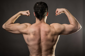 Handsome muscular bodybuilder on gray background, rear view.
