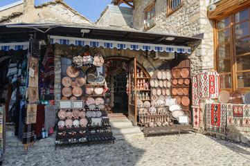 "MOSTAR, BOSNIA - JAN 26, 2018: Open Street touristic market in the old Town, Mostar in Bosnia-herzegovina. The name Mostar itself means ""bridge-keeper"""