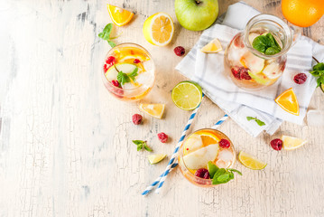 Summer cold cocktail, fruit and berry white sangria with apple, lemon, oranges and raspberry. light concrete background, copy space top view