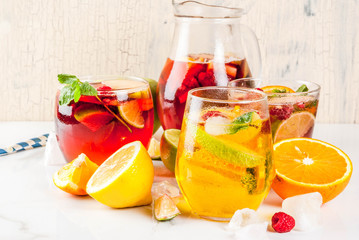 Summer cold cocktail, set of three fruit and berry sangria drink. red white pink, with apple, lemon, oranges and raspberry. light background, copy space