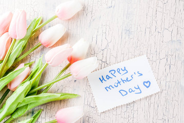 Mother's Day concept, greeting card background. Flowers tulips and greeting note Happy Mother's Day on a light concrete table, copy space top view