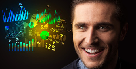 Portrait of a young businessman with colorful charts and graphs next to him on a dark background