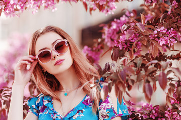 Outdoor close up portrait of young beautiful girl wearing stylish pink sunglasses, necklace, printed dress, posing in street, near spring blooming tree. Female fashion concept. Copy, empty space