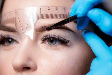 Young woman undergoing eyebrow correction procedure on light background