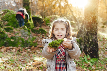 Sweet girl holding a pieces of moss with her brother in background