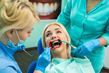 female dentists treating patient girl teeth. Young blonde girl sittiong at the dentist