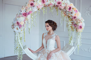 Beautiful young woman with stylish brunette hair and elegant dress posing in luxury white classic room interior with flowers. Spring and summer portrait of elegant lady.