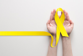 Two hands holding yellow ribbon, symbol of cancer awareness, medical support and prevention with helping hand. Place for text.