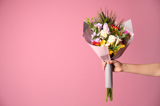 Woman with beautiful bouquet of freesia flowers on color background