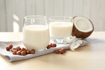 Glasses with milk substitute and nuts on kitchen table