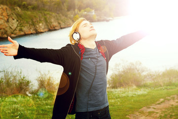 Portrait of young beautiful blond hipster man with headphones standing in nature blessing freedom