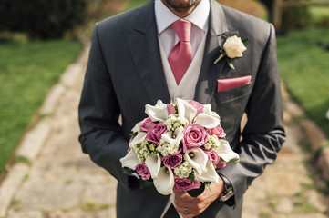 Crop handsome man with bouquet