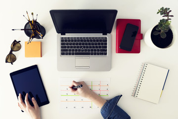 Calendar planner agenda schedule concept. Woman working in her office, planning. Freelance, graphic designer
