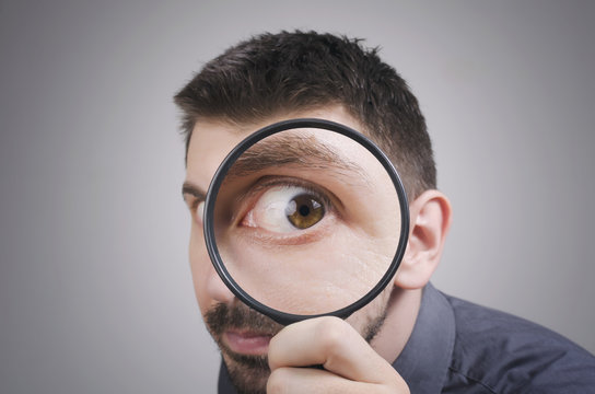 Portrait of a curious man looking through magnifying glass