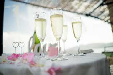 four glasses of sparkling wine at an outdoor beach front wedding reception