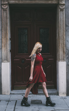 Beautiful young woman in red dress walking in front of old gate