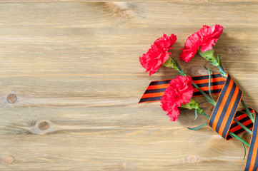 9 May Victory day background. Red carnations and St George ribbon lying on the wooden background