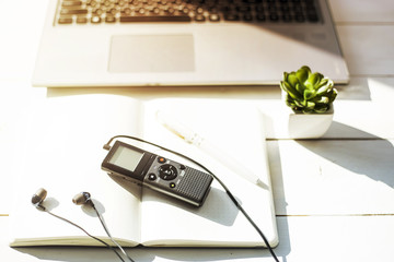 Dictaphone with headphones on a light worktable of a journalist with a notebook, a green succulent and a laptop. In the sunlight